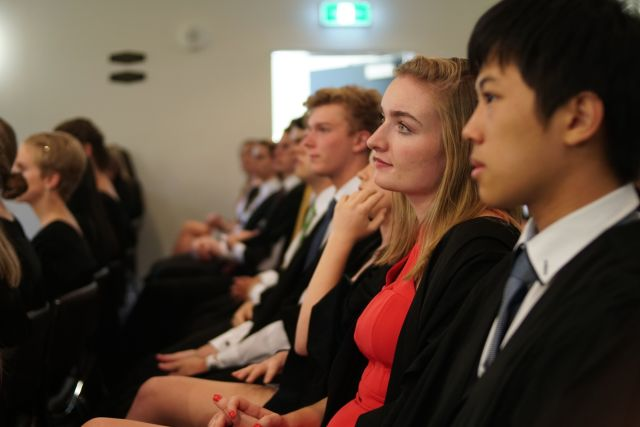 Students in gowns in auditorium