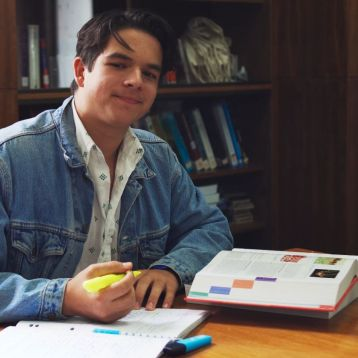 Will with textbooks in the library