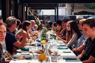 Students at St Hilda's residential college eating under the pergola
